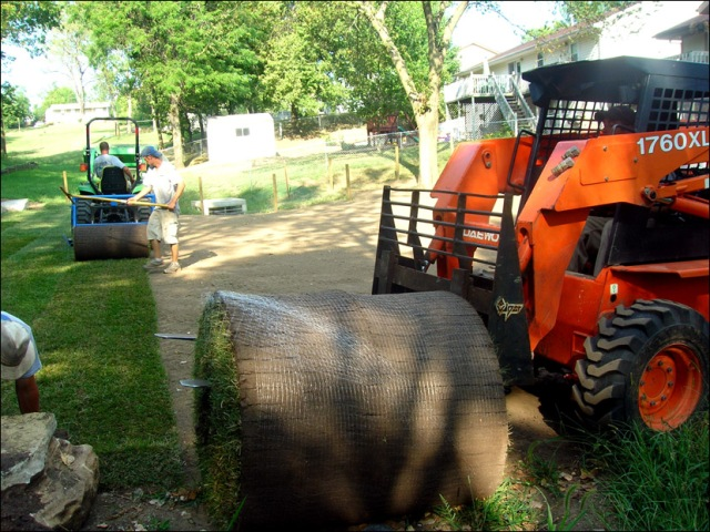Skid loader laying sod roll in Kansas